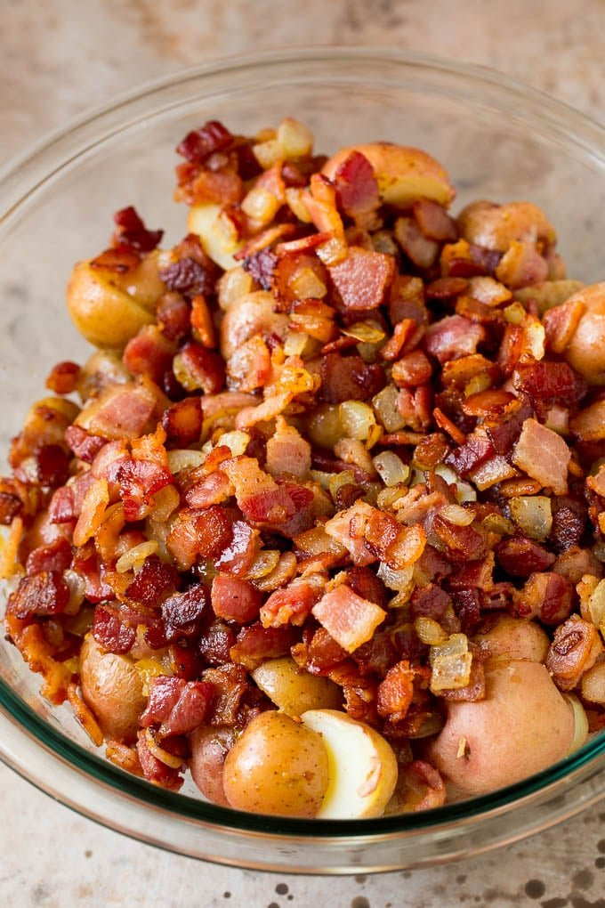 Cooked bacon and halved potatoes in a bowl.