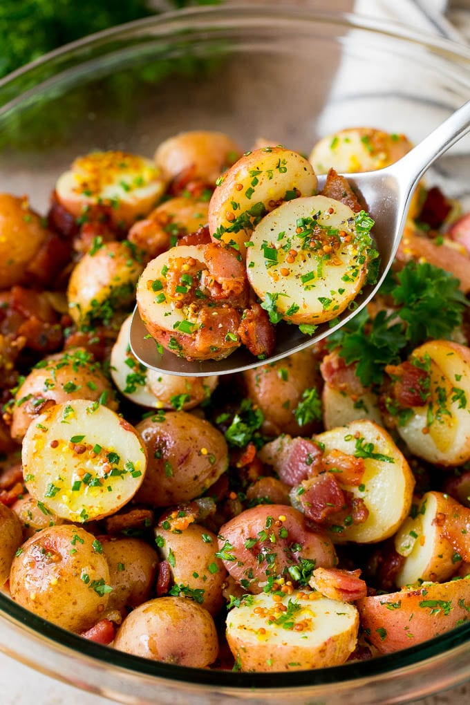 A spoon serving up a portion of German potato salad.