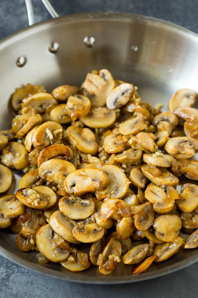 Sauteed mushrooms and onions in a pan.