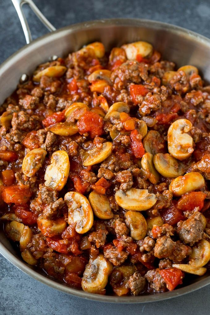 Ground beef, mushrooms, onions and tomatoes in a pan.