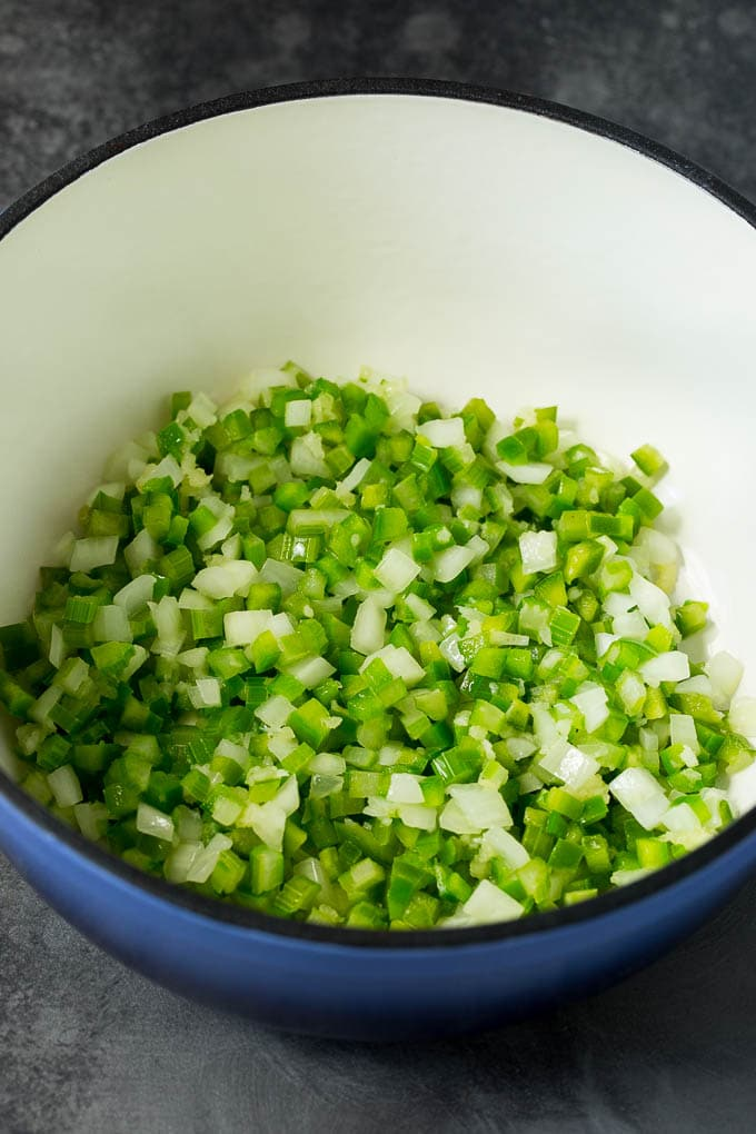 Onions, celery and bell peppers cooked in a pot.