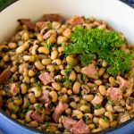 A pot of Hoppin' John made with stewed black eyed peas, ham and vegetables.