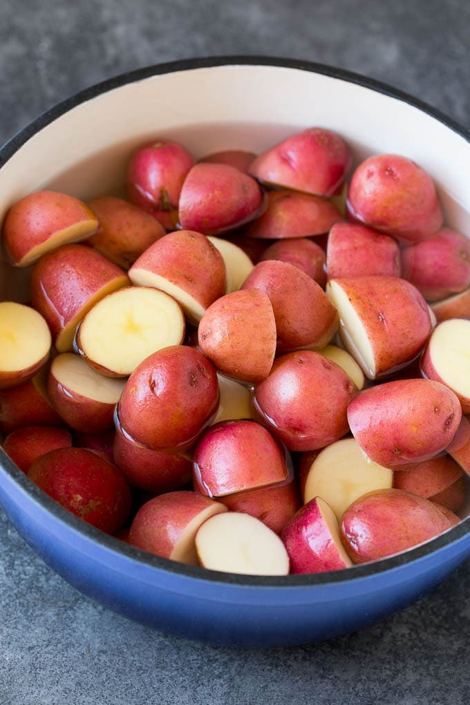 Halved red potatoes in a pot of water.