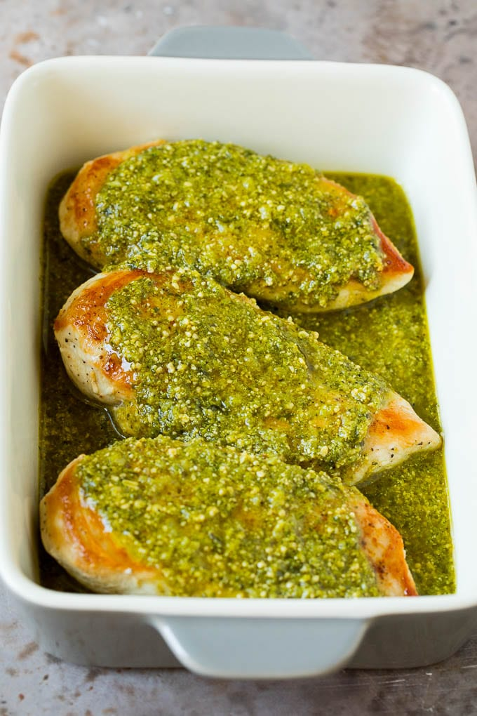Chicken breasts covered in a pesto sauce.