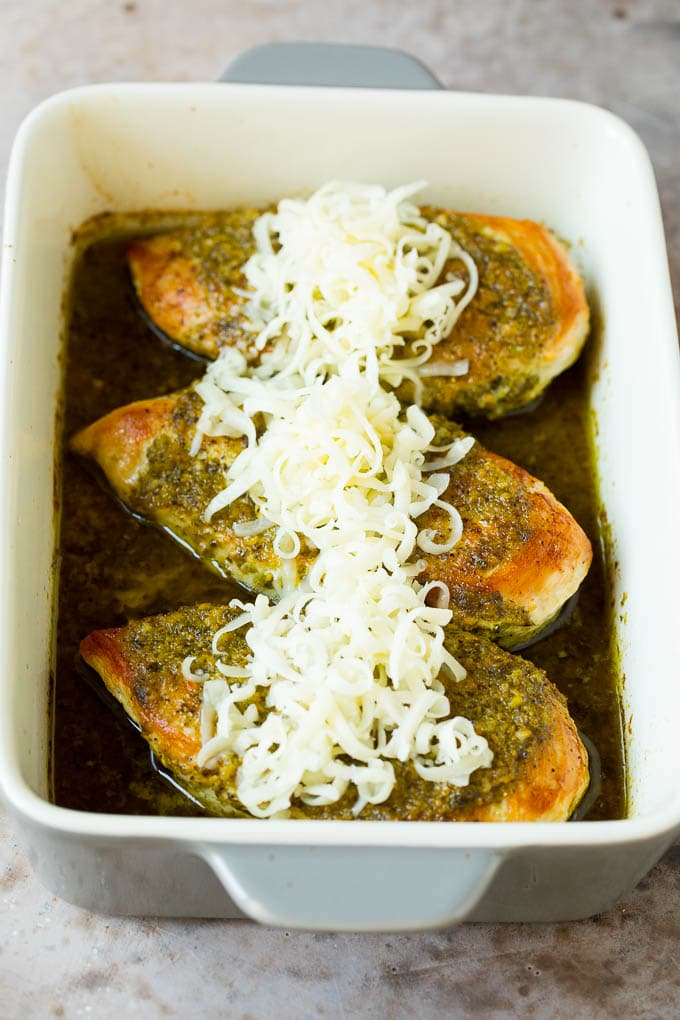 Baked chicken in basil sauce topped with shredded cheese.