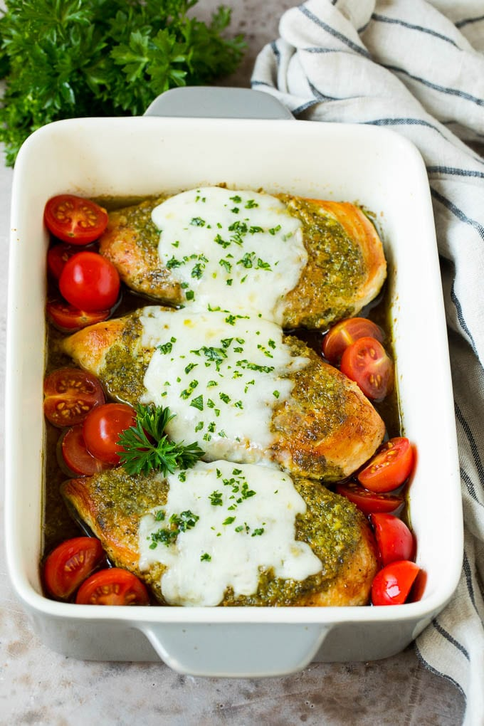Pesto chicken in a baking dish with melted cheese and cherry tomatoes.