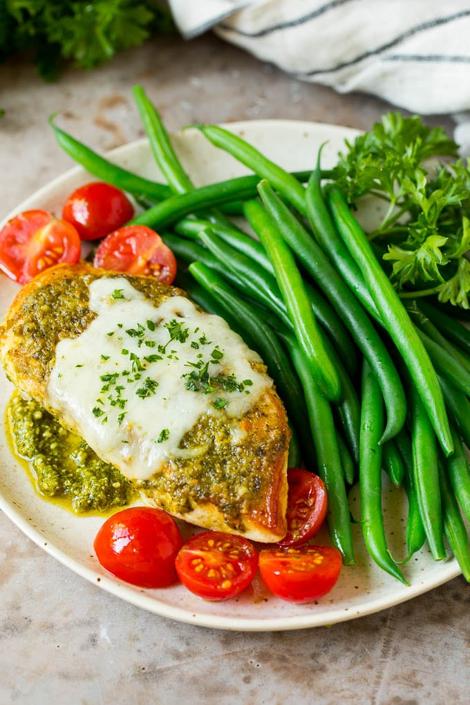 A plate of pesto chicken served with green beans.