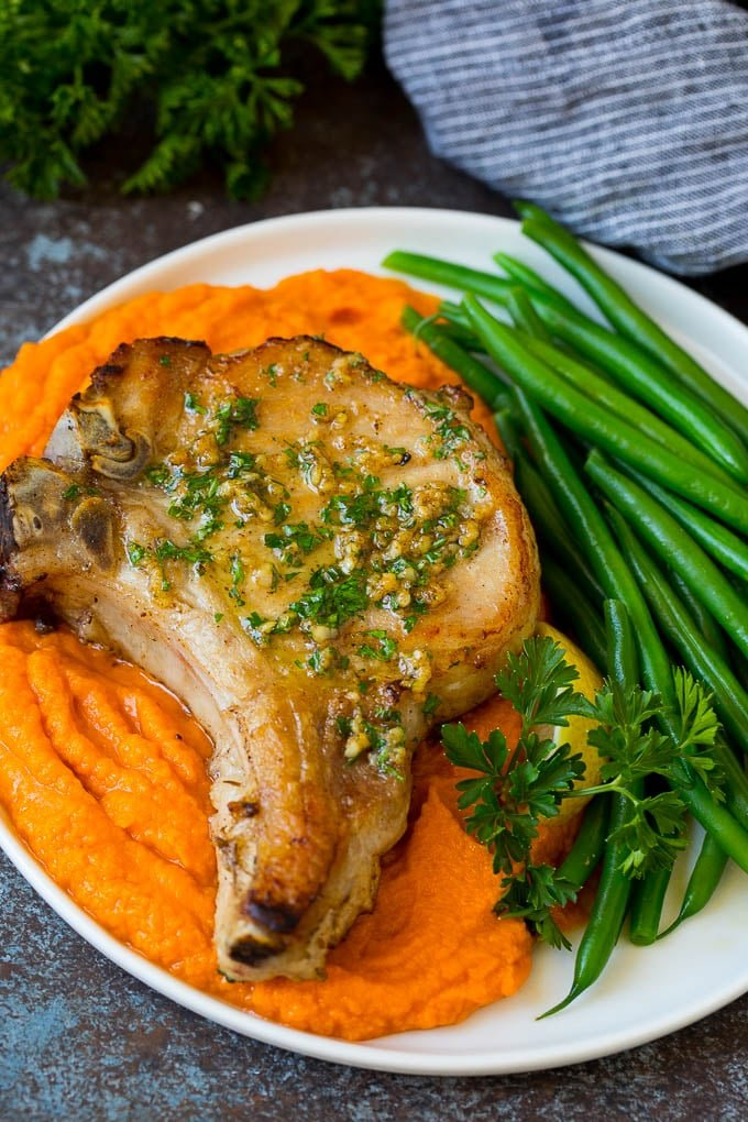 A pork chop served with sweet potatoes and green beans.