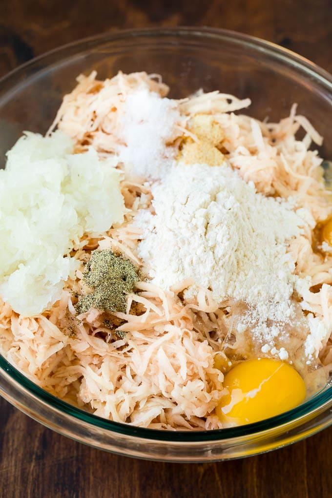 Shredded potatoes, eggs and seasonings in a bowl.