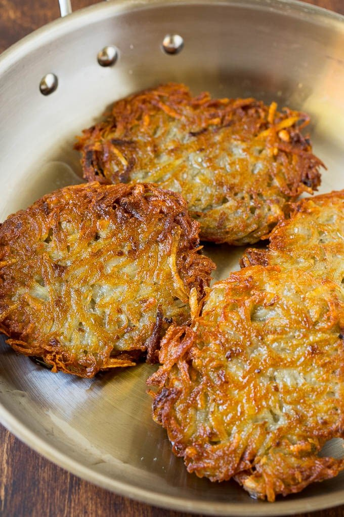 Cooked potato patties in a pan.