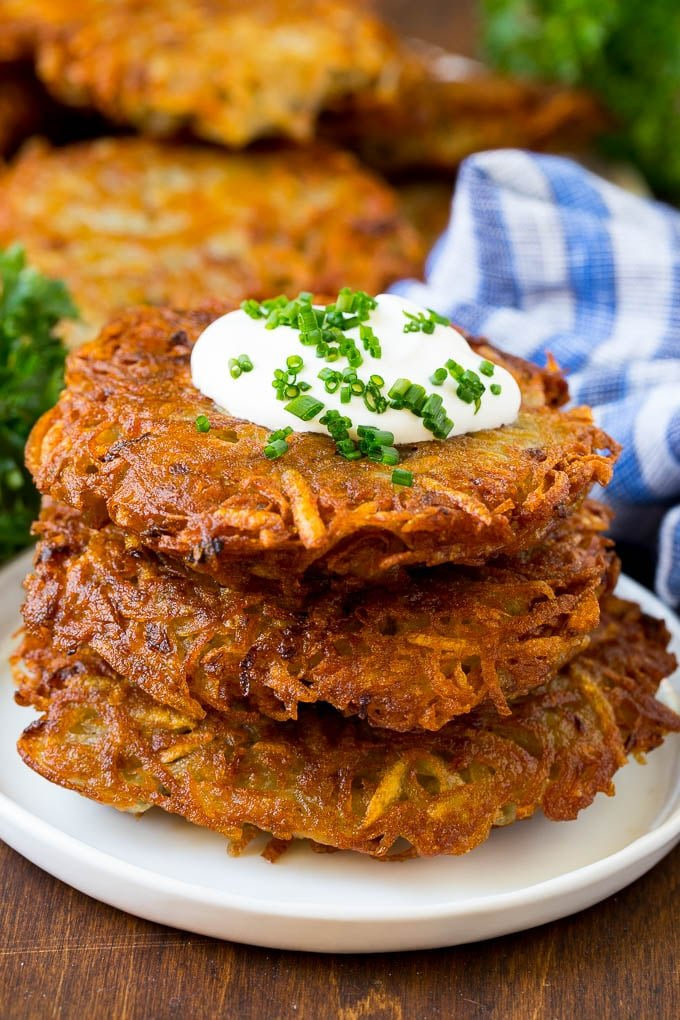 A stack of potato pancakes topped with sour cream and chives.