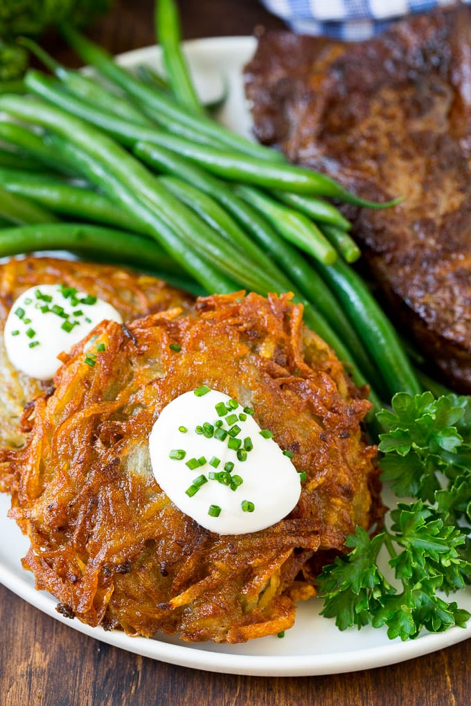 Potato pancakes served with steak and green beans.