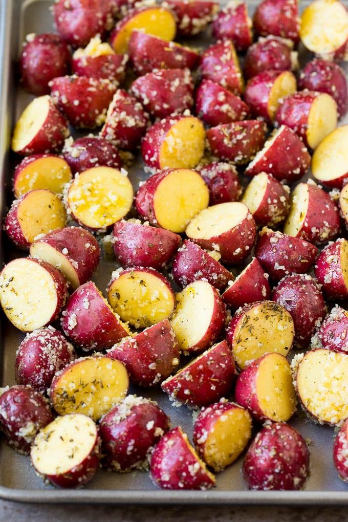 Seasoned potato halves on a sheet pan.