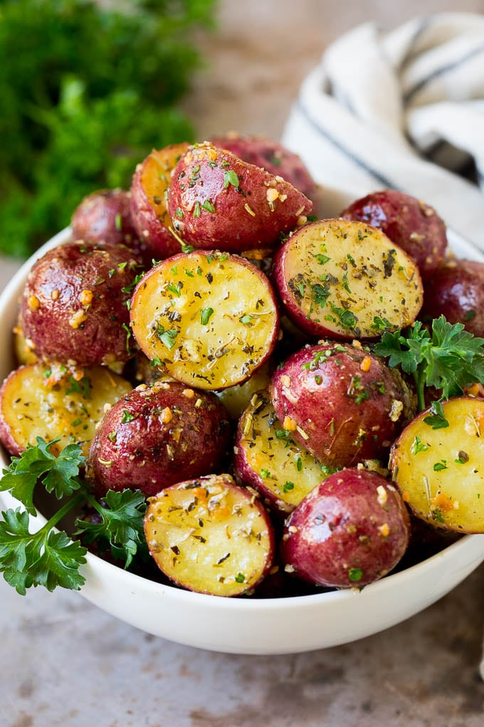 A bowl of roasted red potatoes garnished with fresh parsley.