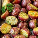 A sheet pan of roasted red potatoes coated in olive oil, herbs and garlic.