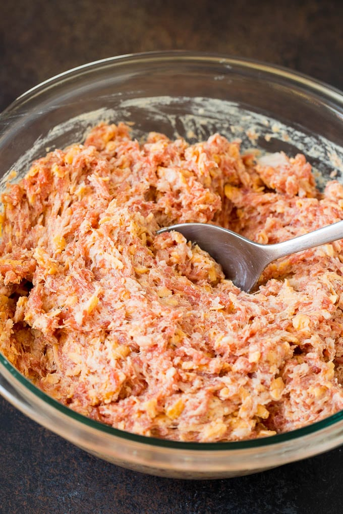 A mixture of sausage, cheese and seasonings in a glass bowl.