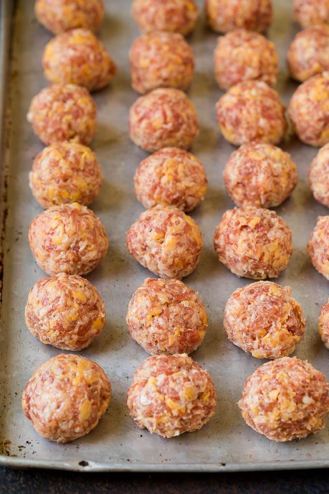 Balls of sausage and cheese mixture on a sheet pan.