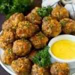 Sausage balls on a plate with a side of mustard sauce.