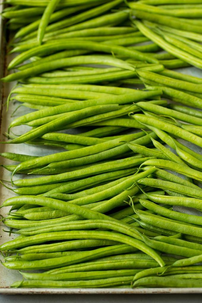 Raw green beans on a sheet pan.