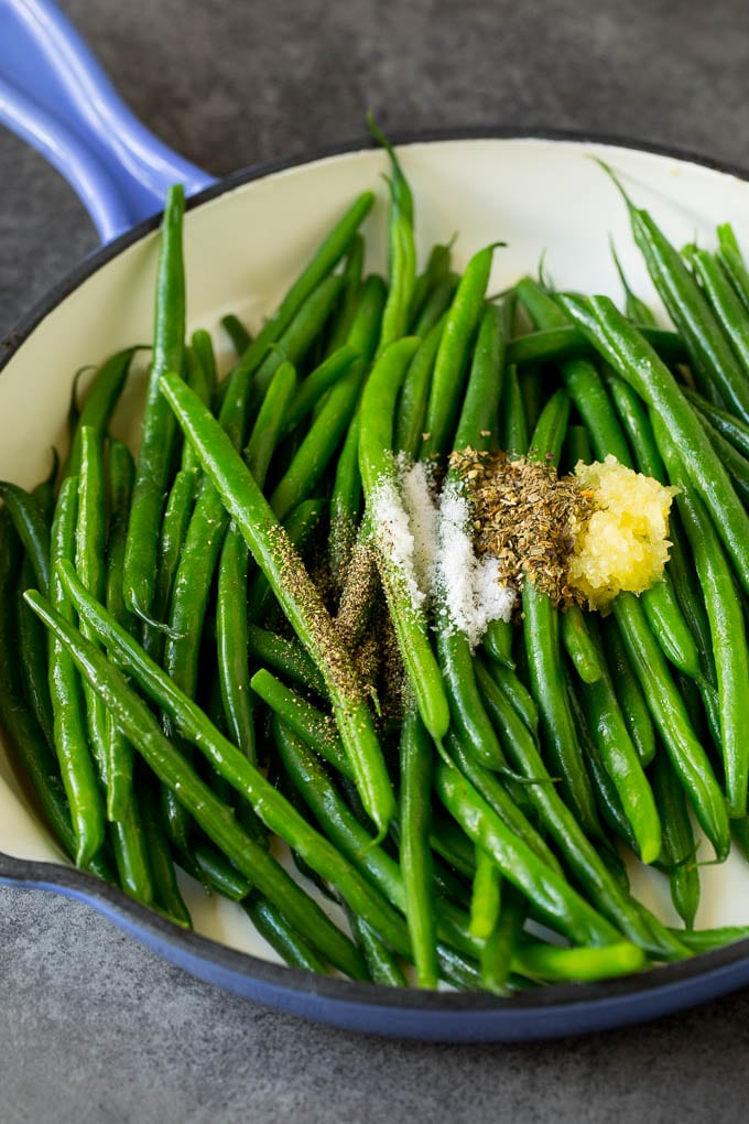 Green beans with garlic and seasonings in a pan.