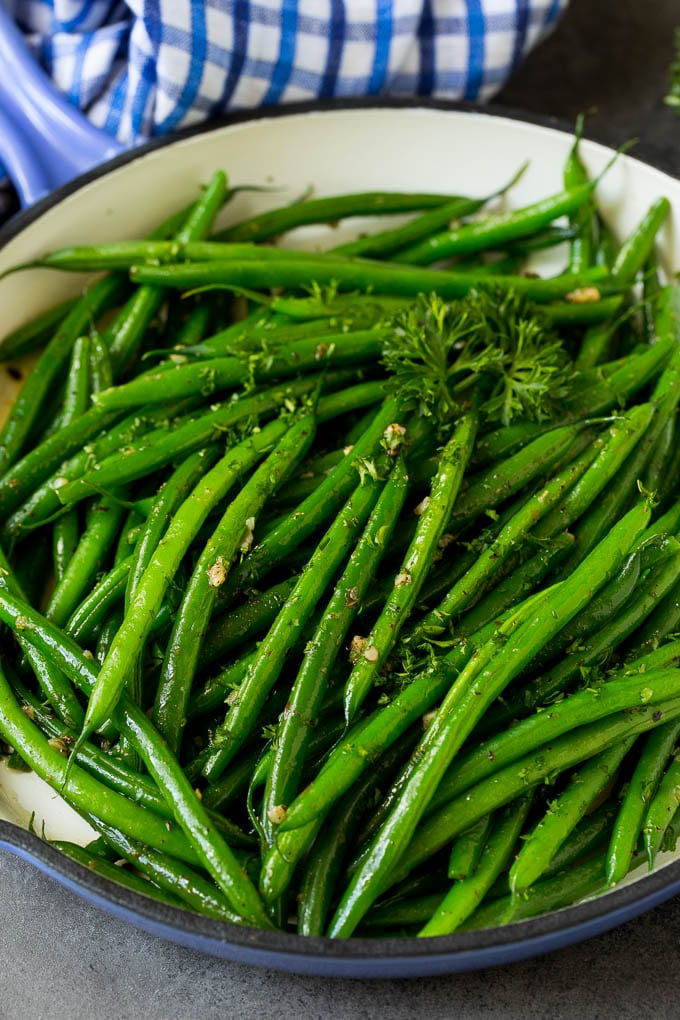 A blue skillet filled with sauteed green beans, garnished with parsley.