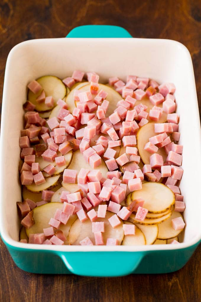 Sliced potatoes and diced ham in a baking dish.