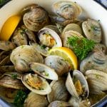 Steamed clams in a pot with lemon wedges and parsley.
