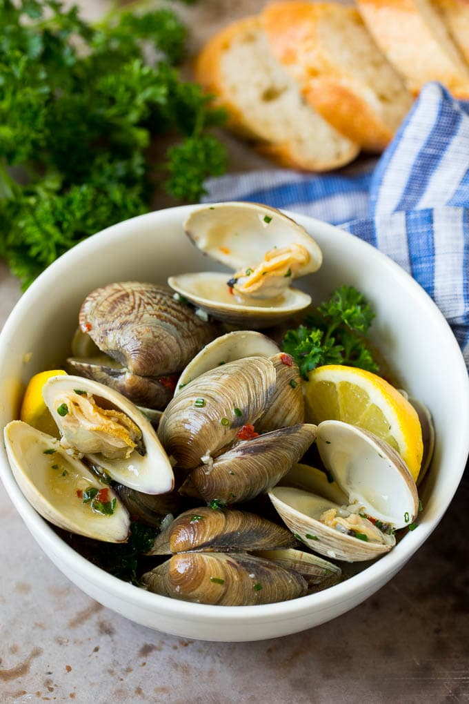 A serving bowl of steamed clams with fresh parsley and sliced bread on the side.