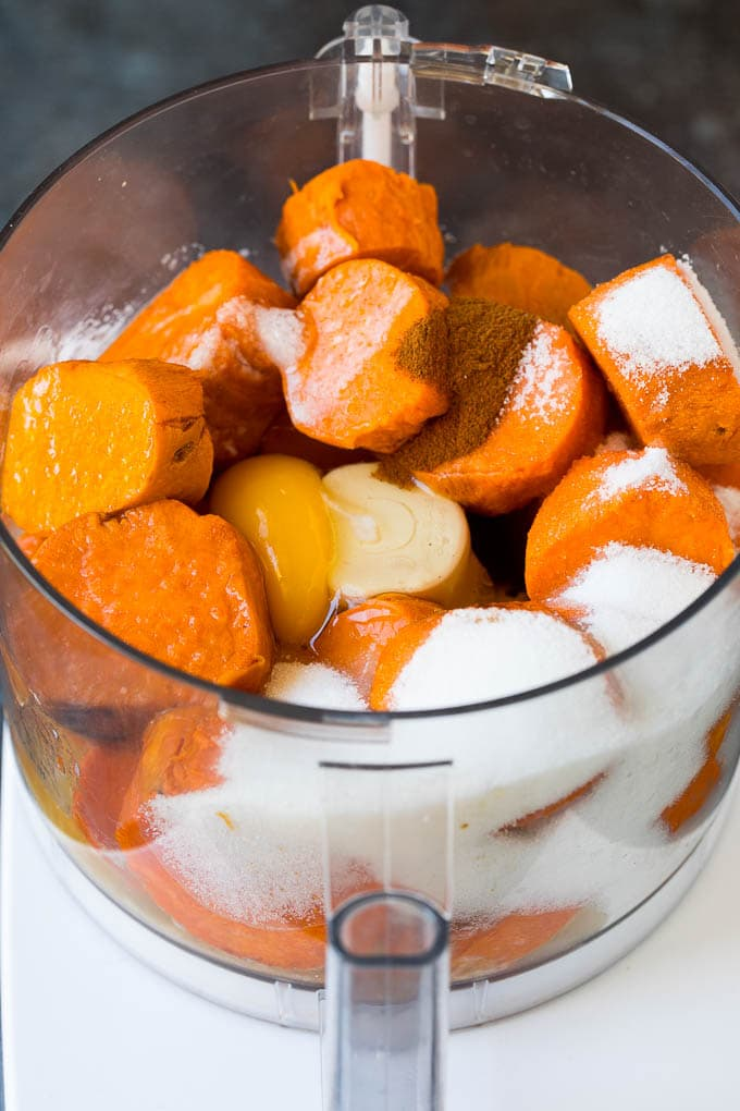 Bir mutfak robotunda küp şeklinde doğranmış tatlı patates, şeker, yumurta ve baharatlar.