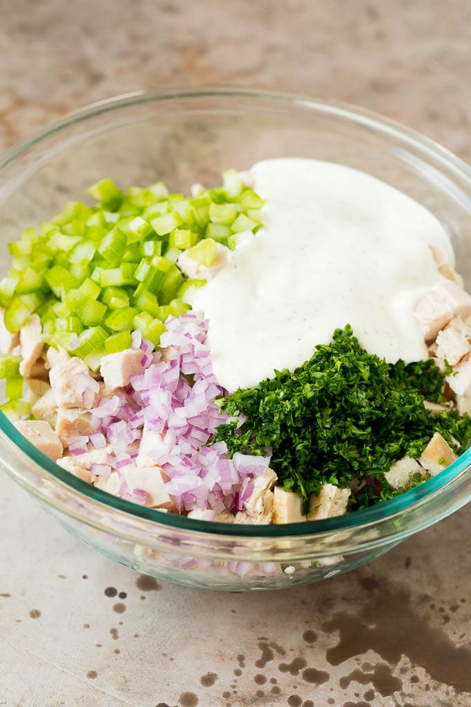 A bowl of turkey and vegetables with a creamy dressing poured over the top.