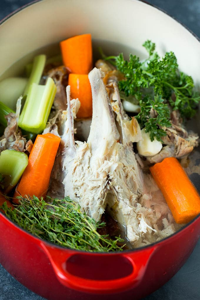 A turkey carcass and vegetables in a pot of water.