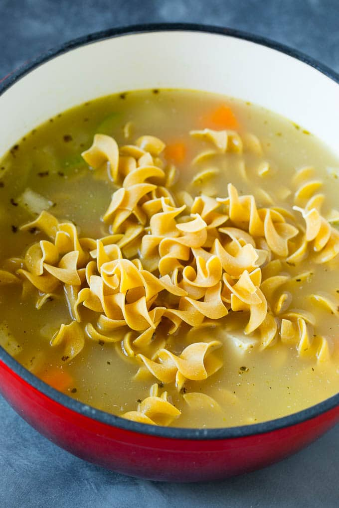 A pot of soup with egg noodles on top.