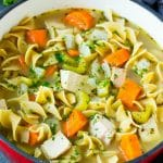 Turkey soup with egg noodles and colorful vegetables in a pot.