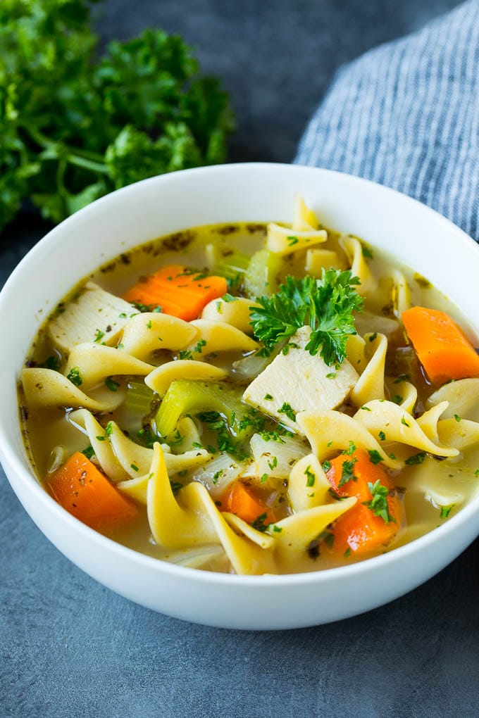 A bowl of turkey soup garnished with fresh parsley.