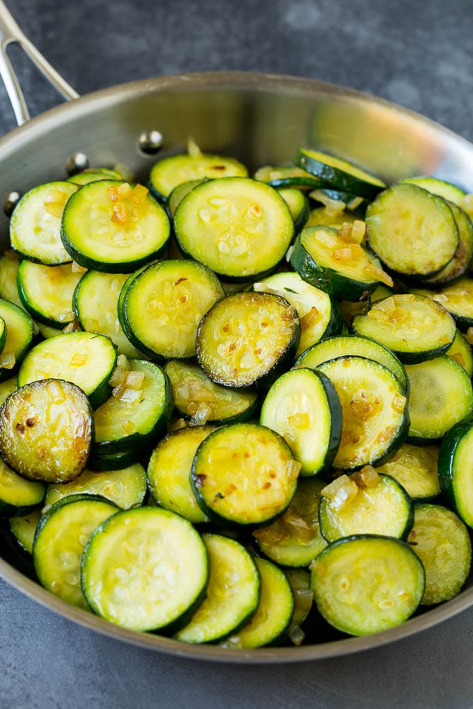 Cooked slices of zucchini in a skillet.