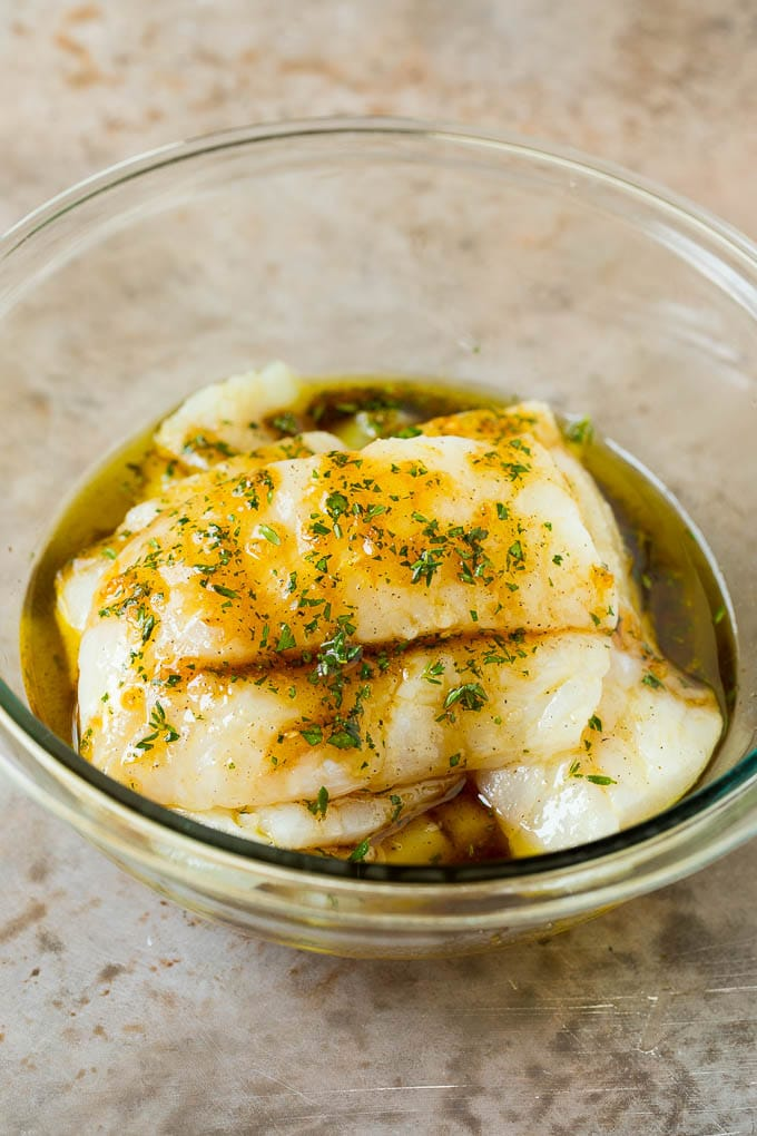 Fish fillets in a bowl of marinade.
