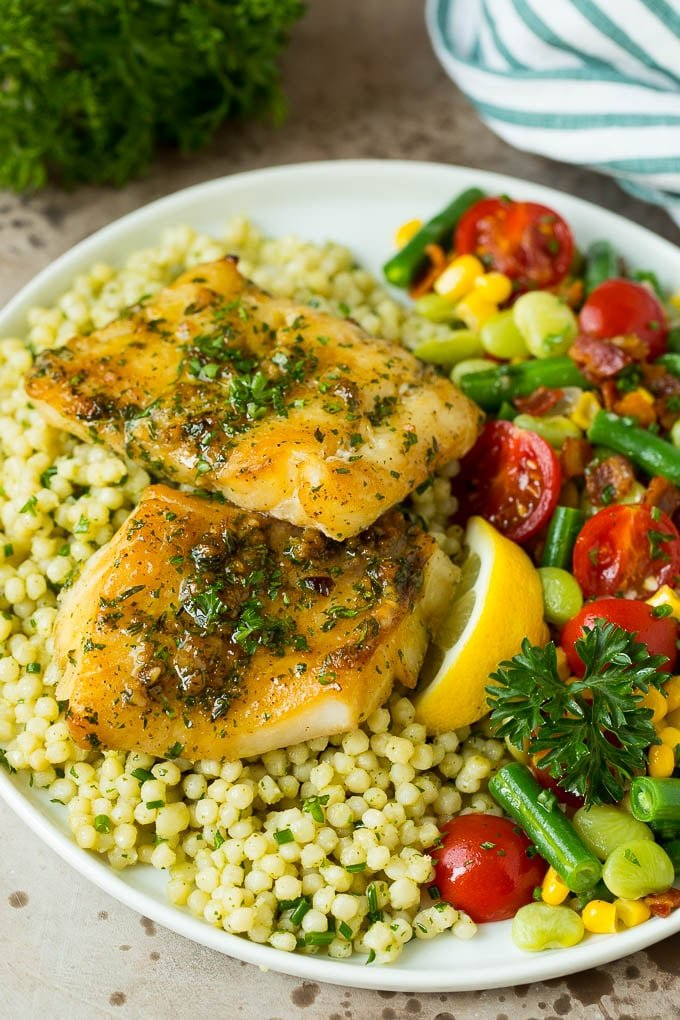 Baked cod served with couscous and mixed vegetables.