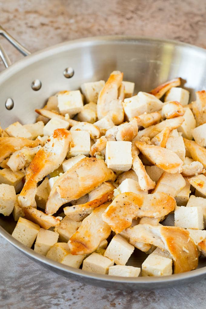 Chicken and tofu sauteed in a pan.