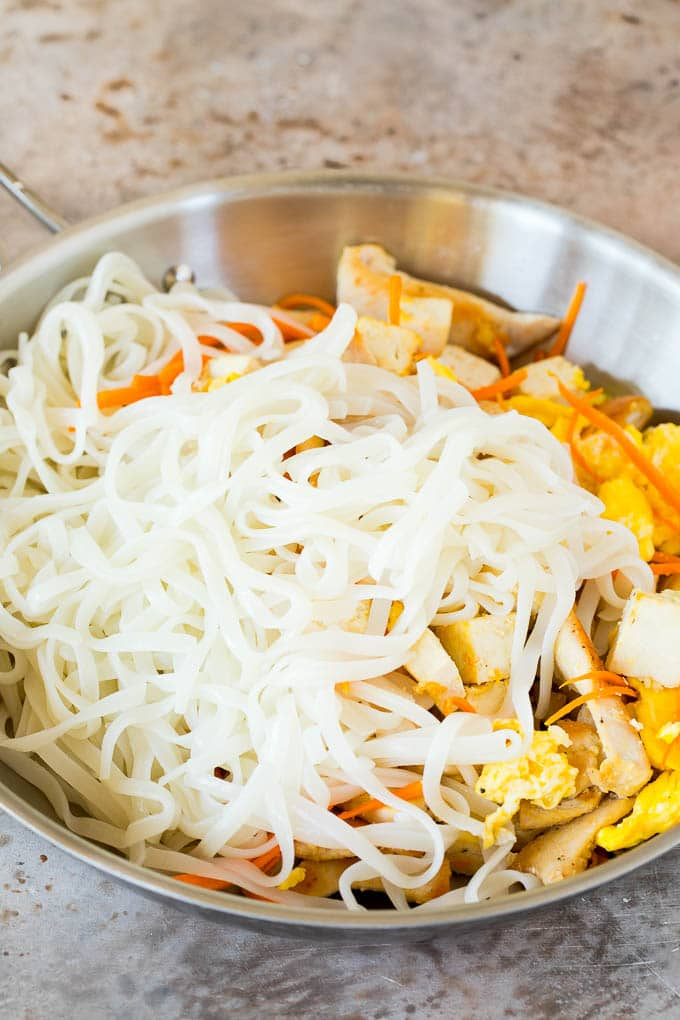 Rice noodles in a pan with eggs, carrots, chicken and tofu.