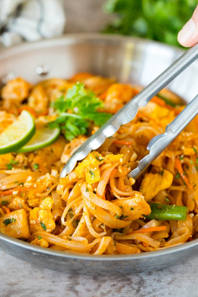 Tongs serving up a portion of chicken pad thai.