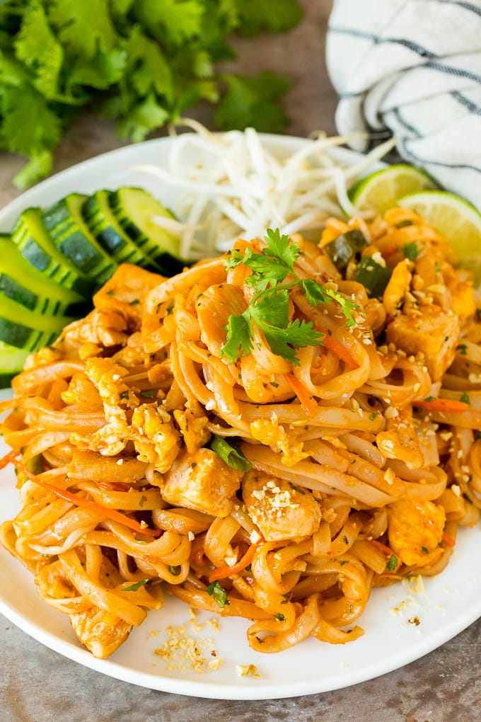 A plate of chicken pad thai served with bean sprouts and cucumber.