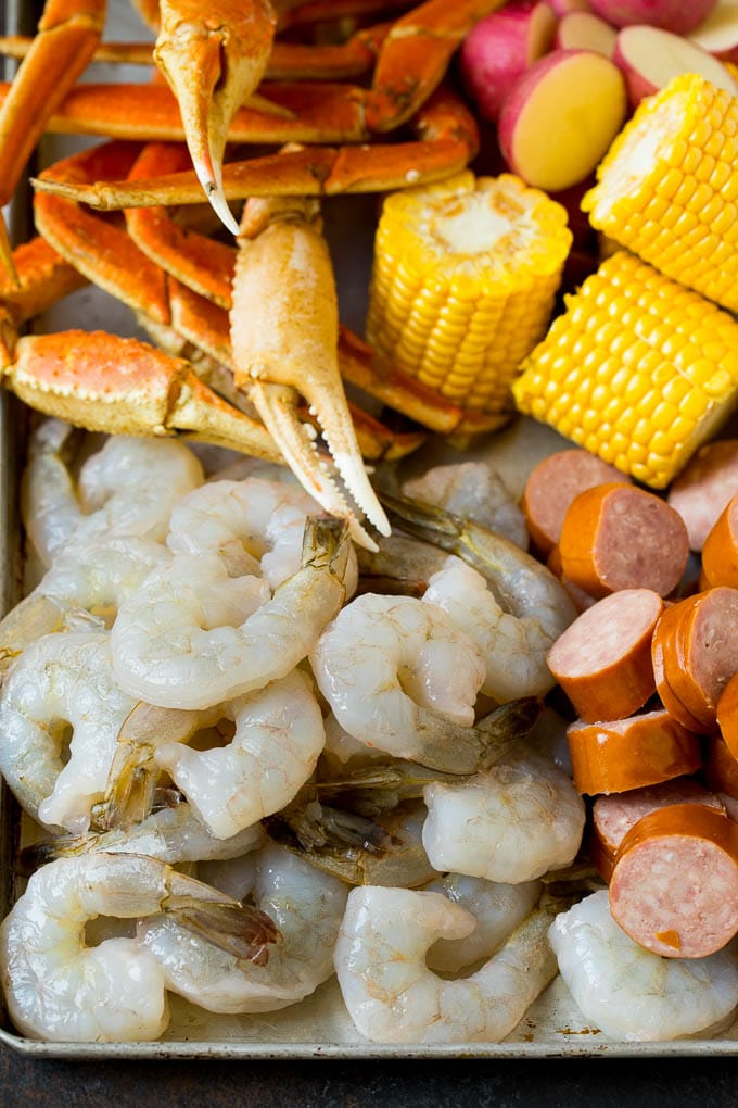 Shrimp, sliced sausage, crab legs and corn cobs on a sheet pan.