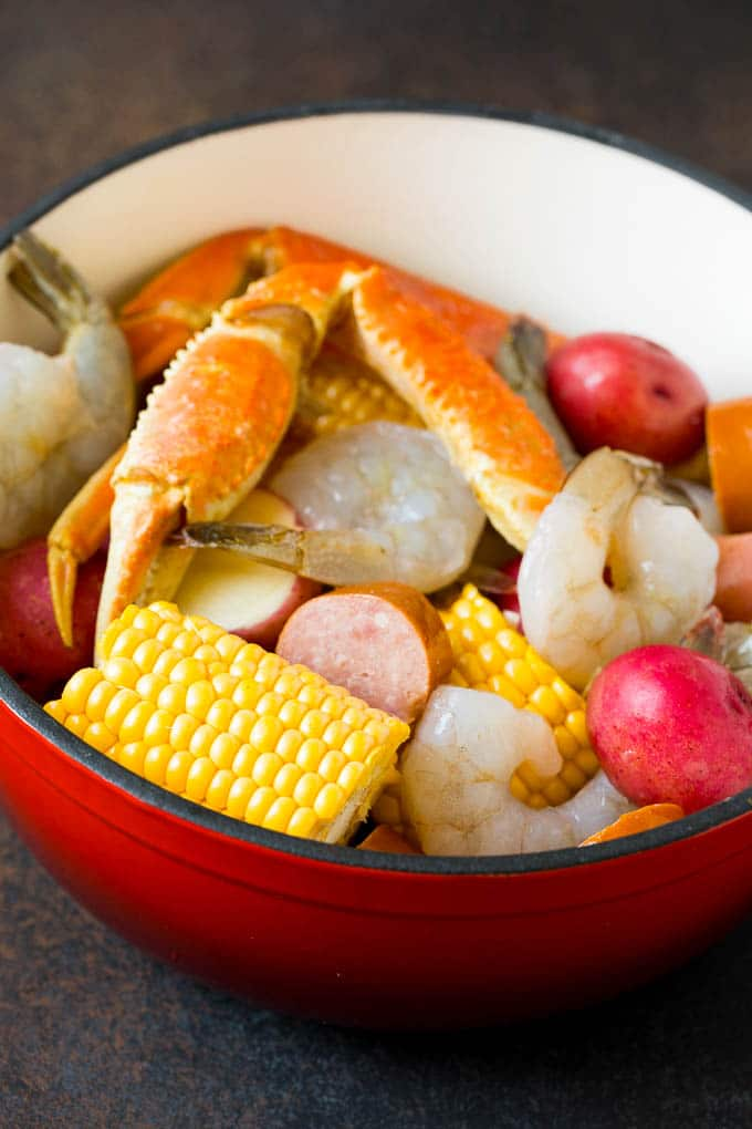 Assorted seafood, sausage and corn in a red pot.
