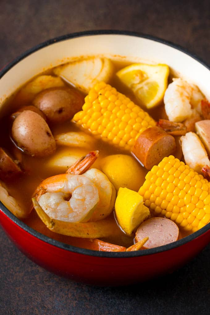 Boiled shrimp, potatoes and corn in a red pot.