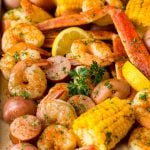 A Low Country Boil with shrimp, crab, sausage corn and potatoes on a sheet pan.