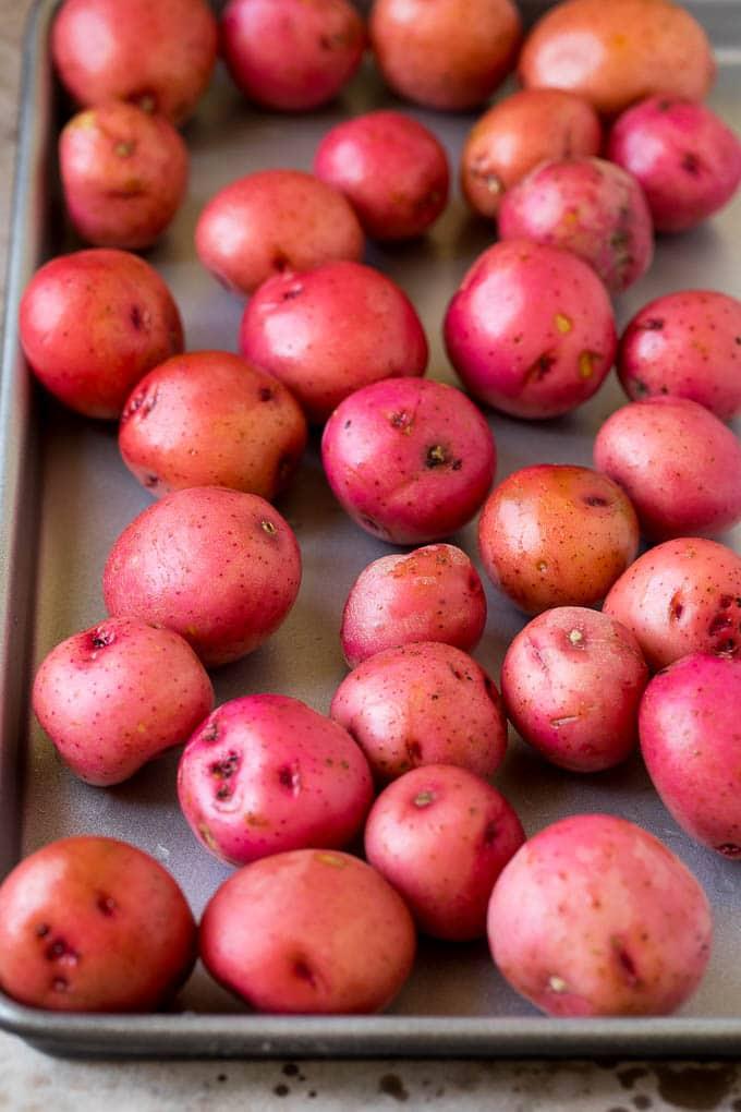 Whole potatoes on a sheet pan.