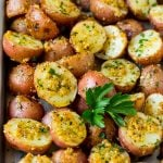 Oven roasted potatoes coated in garlic and herbs, then garnished with parsley.