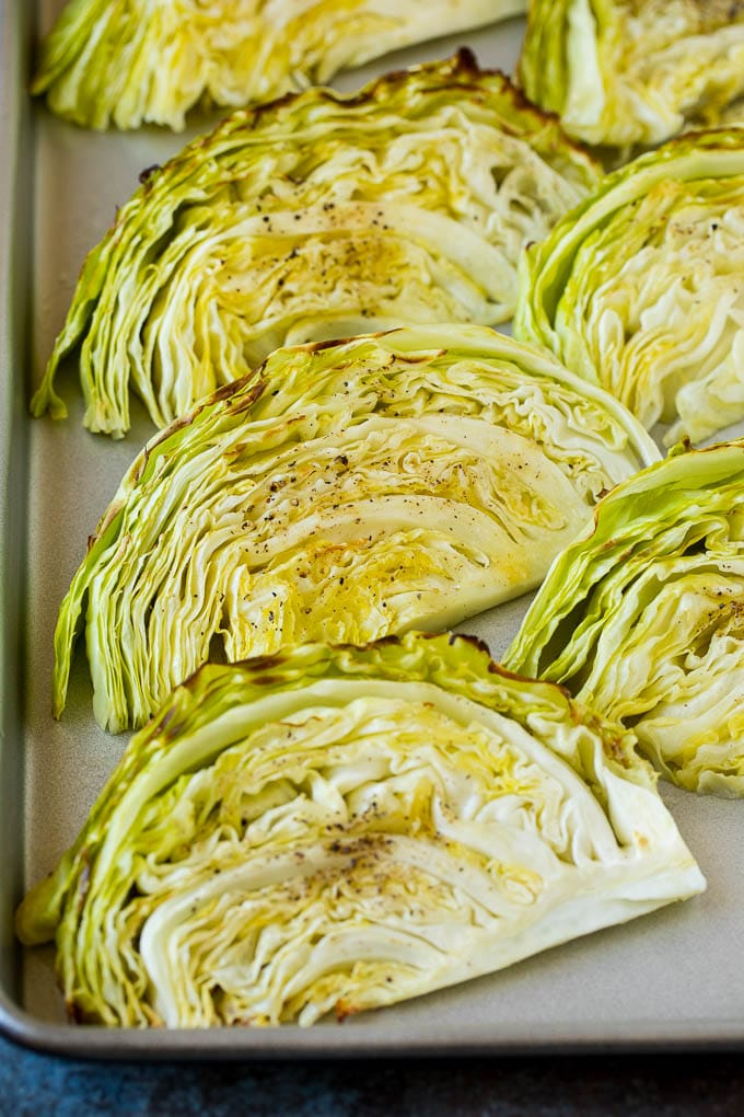 Cooked cabbage wedges laying on a sheet pan.