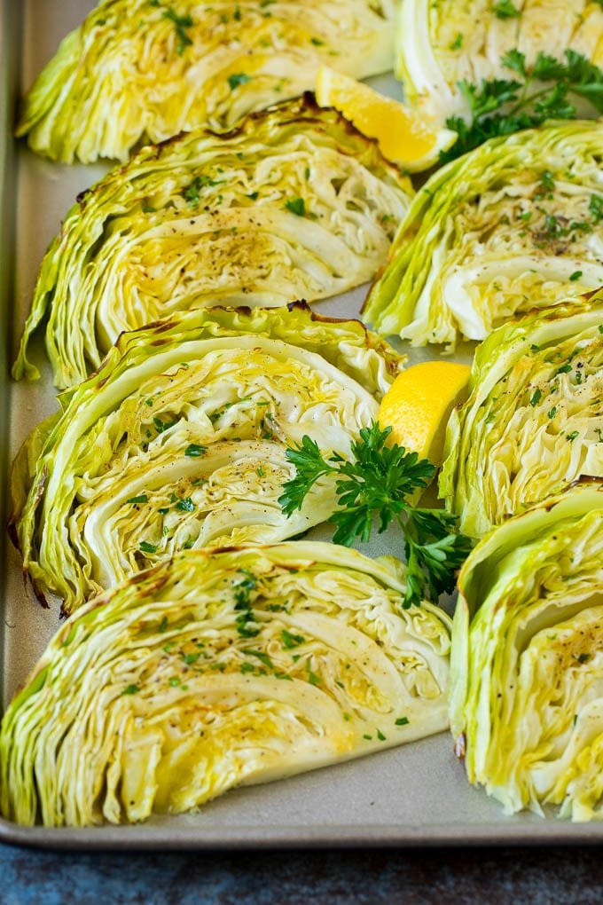 Roasted cabbage on a pan topped with fresh parsley.