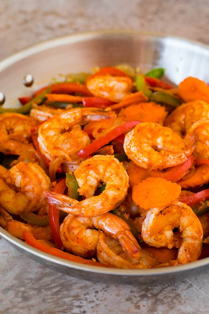 Shrimp, curry paste and vegetables in a pan.